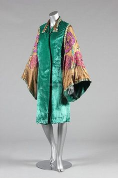 A Maison Worth jade-green velvet orientalist opera coat, circa 1924, bearing narrow ivory ribbon label, the wide cloth of gold furisode sleeves adorned with large beaded and wool embroidered poppies and foliage in mauve-pink and jade, edged in gold braid with green wool embroidered stripes, lined in cloth of gold. Sideway