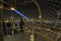View from the top of Eiffel Tower, Paris, France looks out over lights of Paris, while blue laser beam sweeps over city Cheap Hotel Websites, Find Cheap Hotels, Book Hotel Online, A Day In Paris, Hiking Tours, Day Hike, Paris Travel, Best Hotels, Paris France