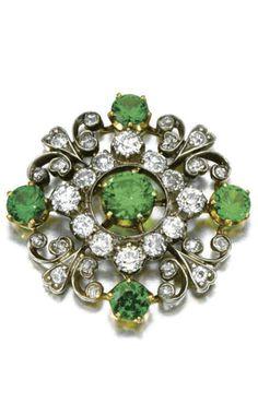 DEMANTOID GARNET AND DIAMOND BROOCH, LATE 19TH CENTURY. Of open work foliate design set with circular-cut demantoid garnets, circular- and single-cut diamonds, detachable brooch fitting.