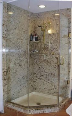"Private Residence, North Raleigh. This pre-existing shower was ""dressed up"" by the addition of slabs of granite on the shower walls. Use of the glass shower door trimmed in brass accents the stone nicely. The granite is Shiva Kashi. We discourage the use of marble and limestone in wet-to-"
