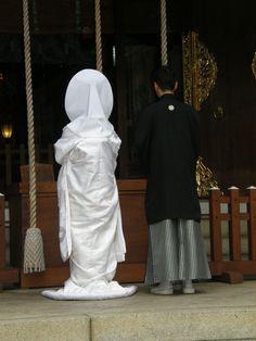 Japanese bride and groom wearing traditional wedding kimono, praying at a shrine