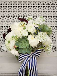 White and green wedding bouquet tied with navy striped ribbon
