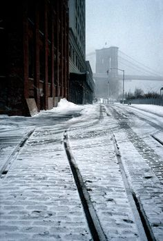 Alex Webb - New York City. 2005. Along the Brooklyn waterfront showing old rail lines and Brooklyn Bridge in blizzard.