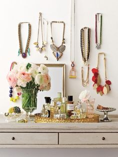 1. Hooks: Dangling from ornate hooks (or even clear pushpins), necklaces double as decoration. 2. Candy Jars and Pedestals: Whimsical, easy-access storage for bracelets and rings. A vanity tray completes the ladylike tableau and a collection of vintage perfume bottles adds extra sparkle.    My dresser at home looks similar to this and I love it!