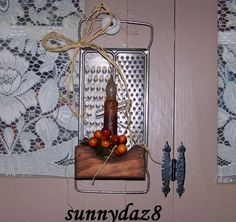 The vintage grater was repurposed to be a candle holder for a battery operated candle.  The candle cup is decorated with berries.  I have it hanging from my cabinet door. It  will soon be listed  on ebay.  My seller ID is sunnydaz8.  Sold on ebay
