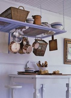 old door suspended from ceiling used as a shelf and to hang pots and baskets