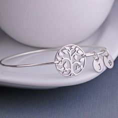 A sterling silver circle tree of life measuring approximately 3/4 inch is the center of this bracelet. Each bangle is...