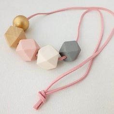 Geometric girl's necklace made from painted wooden beads on a suede cord.Cord measures 80cm in length and can be re-tied for a shorter length necklace so the necklace is suitable for both big girls and little girls.WARNING! Choking hazard - small parts. Not for children under 3 years. And please do NOT let babies chew on the beads. Caring for your jewellery: please avoid getting the necklace wet or spraying it with perfume.Each necklace is handmade and unique, pl...
