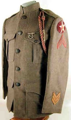 """Wool tunic of Cpl of the 6th Machine Gun Battalion; bronze eagle and anchor buttons, pleated pockets and pointed cuffs. Left sleeve displays applied wool construction red and yellow Indian head worked through with black and white thread details, on a white star sewn to a purple velvet oval field, cuff with three gold braid service chevrons; both sleeves with green on red rank chevrons. Tunic also retains a silk Fourragère to the French Croix de Guerre and a silvered M1912 """"EXPERT RIFLEMAN""""…"""