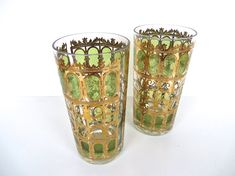 Set of 2 vintage tumblers by Culver in the green Scroll pattern for your home bar. Glass features heavy 22kt gold applied scroll work with a green textural background almost giving it a stained glass effect. Bottom weighted and heavy in the hand, tumblers each measures 5 1/2 H x 2