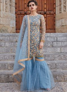 Baby Blue Embroidered Net Gharara Suit features a net kameez with santoon inner, net bottom with santoon inner and net dupatta. Embroidery work is completed with zari, sequins, stone and lace embellishments on this style. Indian Fashion Dresses, Dress Indian Style, Indian Designer Outfits, Indian Outfits, Sharara Designs, Pakistani Formal Dresses, Pakistani Dress Design, Pakistani Gharara, Stylish Dress Designs