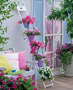 A very pretty way to add a splash of floral color to a deck or patio, especially if space is limited.  (I would just make very sure that the footings of the ladder trellis are very stable and secured so that they don't slip!)