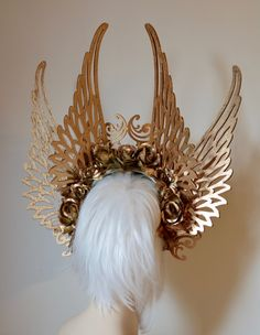 Crown yourself victorious, with this multi-winged, golden work of art, designed to make its wearer feel like a goddess. Made with lightweight, hand painted, wood cut-out wings, faux flowers and a lions paw shell, this piece is loaded with love and devotion. It is lined with lace covered felt for your comfort, and is secured by an elastic strap that sits behind the head. To find out more about my life, art and work, visit me on: my website - http://www.serpentfeathers.com/ I...