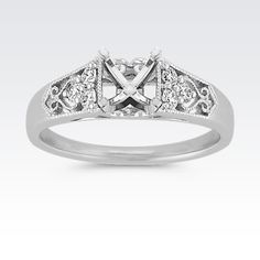 Sweet but striking, this diamond engagement ring focuses on the vintage design with milgrain detailing and two trios of diamonds. The trios include six round diamonds, at approximately .19 carat total weight, crafted in quality 14 karat white gold.