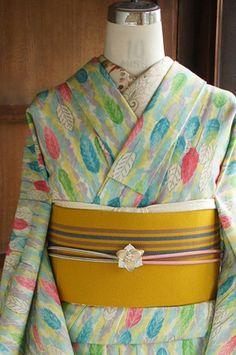空色やこっくりピンク、黄色や緑、グレーの優しいカラーと、パステルで描いたような素朴なタッチも愛らしく織り出された、木の葉のような鳥の羽のようなデザインに心ときめくウールの単着物です。