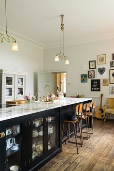 Glazed base cabinets and a tongue and groove panelled breakfast bar area with quirky vintage bar stools and ornate lighting