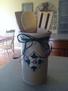 Purchase a small crock and buy sticker paper and print your unit crest or logo on the computer and slap it on there!  Fill with kitchen tools or flowers or whatever and tie off with a nice bow!