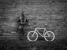 Man Standing By Bicycle On Field Against Wall