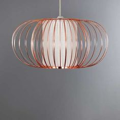 Crafted from copper, this oval ceiling pendant features a curved design with a white parchment centre....