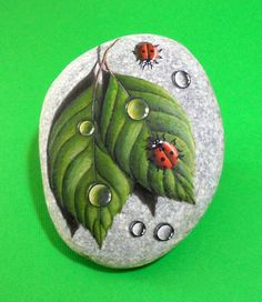 A Natural flat rock from the beach is hand-painted with red ladybugs on wet green leafs! A preety handmade painted stone made by for your home decoration or to make a pretty gift to your loved ones!  Is painted on a flat sea stone which i have collected from a beach on a Greek island. Is painted with fine art quality acrylic colors and very small brushes for the detail, signed on the back and covert with strong glossy varnish for protection. Although the varnish that is covet makes it…