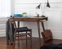 Scandinavian Designs - Mid-century style defines the Arbete desk featuring a warm walnut stain and splayed tapered legs. Two streamlined drawers and a niche on each end make this desk a paragon of form and function combined.
