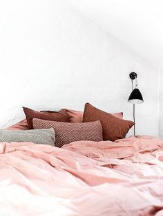 Scandinavian bedroom with white walls, a black sconce and salmon colored bedding