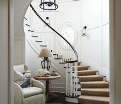 This sweeping staircase is gorgeous. A cozy vignette at the foot of the stairs is inviting. - Traditional Home ® / Photo: Colleen Duffley / Design: Tammy Connor Foyer Staircase, Curved Staircase, Entry Foyer, Staircase Design, Staircase Handrail, Staircase Remodel, Staircase Ideas, Front Entry, Winding Stair
