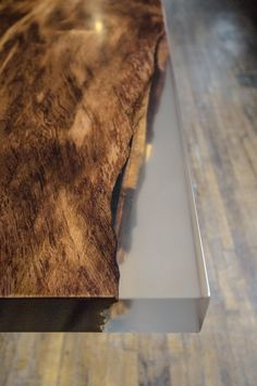 "This 2500-4000 year old redwood burl table top is certified through the Forest Stewardship Council. It is ""square-cut"" and contains clear, cast resin in each of its natural voids. The table top is paired with the STACKLAB Band Ribbon legs finished in either antique pewter (shown) or brass."