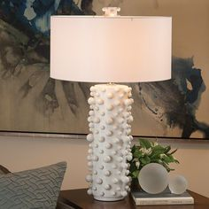 """Spheres of varying sizes are playfully bound to these cylindrical ceramic lamps. In fact, it's a skillful feat to produce each base in full molecular detail from one mold. Available in matte white and graphite. Holds a 60 watt Type A lamp bulb. 8 foot clear cord; switch on socket. Round drum hardback shade covered in ivory silk.  Shade Dimensions: 20""""Dia. x 10""""H Round drum hardback shade covered in ivory silk  Base: 8""""Dia. x 32""""H 8' Clear Cord, Swtich on Socket"""