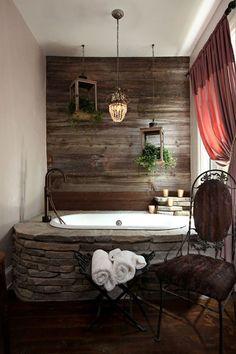Rustic bathroom design with raw wood wall, stone tub, & drop lighting Stone Tub, Wood Stone, Rustic Stone, Rustic Wood, Rustic Feel, Rustic Modern, Rustic Decor, Weathered Wood, Rustic Charm