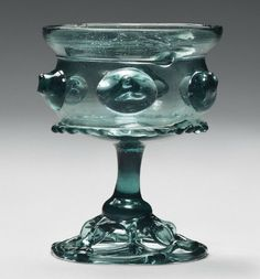 A STEMMED-GLASS (KRAUTSTRUNK) CIRCA 1500, GERMAN Of watery-green tint, the compressed bowl with an everted rim above a thread, applied with a band of prunts above a pinched collar, on a baluster stem supported by an openwork foot 4 5/8 in. (11.5 cm.) high