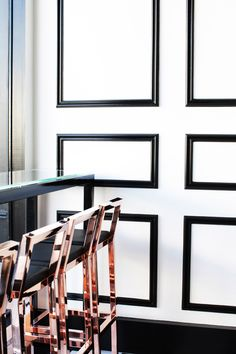 black painted wainscoting. trim. rose gold. bar stools. modern.