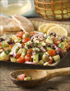 Tomato and Cucumber Salad - This Greek-style salad with tomatoes, cucumbers, red onion, olives, feta and fresh lemon juice is the perfect summer side.