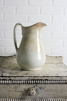 An old cabinet with original paint, an ironstone pitcher against a painted brick wall. White Dishes, White Pitchers, Ceramic Pitcher, Shades Of White, Home And Deco, Vintage Decor, Vintage Crockery, Shabby Vintage, Rustic Decor