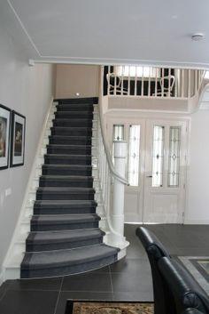 Klassiek bekleedde trap. Door je trap te voorzien van een luxe traploper in de zelfde kleuren als je vloer, laat je de ruimte als het ware doorlopen naar boven. Hierdoor oogt de ruimte nog groter. Daarnaast is er hier bij de trapbekleding gekozen voor een donkere bies, wat het geheel een chique uitstraling geeft.