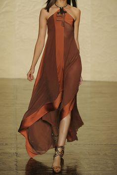 Donna Karan's two-tone halter gown is a standout from the 2014 spring runways. Mimicking the draping of a scarf, the silk-satin trimmed stretch-silk design falls in flattering brick-hued layers. Amp up the glamor with stacked cuffs and multi-strap sandals.