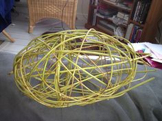 Willow bird - Stage 1 -  Make a hoop and 2 tear drop Put the three part together to make what looks like a torpedo!  Tape in place, then replace the tape with a X lash of fine willow. Start to free weaving around the rods by securing the tips in the hoop (wedging the tips between the rods of willow that make the hoop).