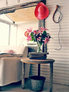 Designer Tricia Rose created this side table using rope and driftwood, two found elements with a coastal vibe. Even a colorful sun hat becomes part of the decor in a seaside cottage.