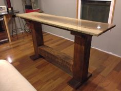Reclaimed pedestal bar height cocktail table with granite top.