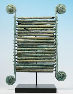 An ancient Greek bronze chalcophone, a musical instrument, composed of nineteen bronze tubes suspended on wires between two vertical side pieces with spiral terminals acting as resonators.