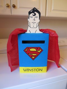 Superman Valentine Box -- Cereal box, $1 t-shirt from Dollar Tree cut and glued, manilla folder head, free logo printed, red tissue paper. Pic looks large. Total height to top of head is only 17 inches. My Funny Valentine, Valentine Day Boxes, Valentines For Boys, Valentines Day Party, Valentine Day Crafts, Projects For Kids, Holiday Fun, Classroom, Box Tops