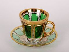 A glass cup and saucer in green and gold. Czech Republic, Moser, 1920-1930. Early 20th century art glass.