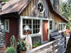 Step inside this small woodland cabin oozing rustic charm: Love the siding and the round window in the gable end
