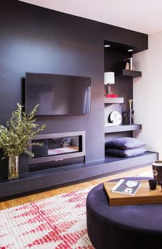 Living room with a contrast black wall with  a handing tv and shelves