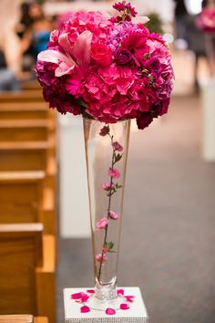 The church aisle was decorated along the sides with glass vases filled with cherry blossom branches. Pink arrangements of hydrangeas, lilies, and roses sat atop each vessel. Photography: D. Park Photography. #weddingceremony #decor Read More: http://www.insideweddings.com/weddings/a-black-white-pink-wedding-in-august-inspired-by-cherry-blossoms/617/