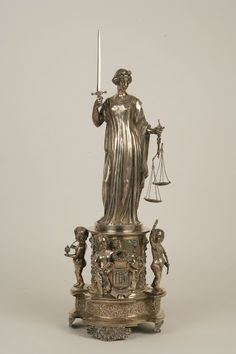 The Justice      1849      Real Fábrica de Platería Martínez        This silver sculpture is an allegory of Justice, identified by the symbols hold by the female figure, the sword and the scales.