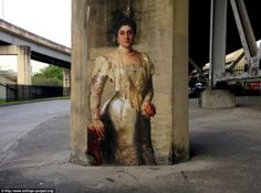A portrait of a grand fin-de-siecle society lady draped in lace and pearls is adorned on a gritty concrete underpass in New Orleans
