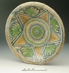 """Collection place: Southwark, London [Southwark] or Aldgate, London [City of London] 1601-1635 Earthenware H 60 mm; DM 303 mm; DM (footring) 102 mm Museum Section: Post-Medieval Summary: English tin-glazed ware charger with a central rosette in blue with green shading, surrounded by triangles in ochre, and pale green foliage, outlined in blue, on an off-white glaze. From a brick- and chalk-lined well at the W end of the site, half in the S side of the central cutting, 8"""" from the retaining…"""