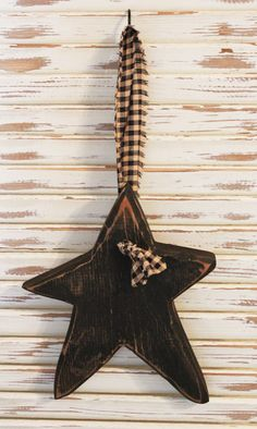 This Primitive Hanging Star is great for hanging on door knobs, drawer pulls, the wall or anywhere else you choose. It is approximately 6 x 8 x 3/4 and is made from wood. No two stars are alike as each one is hand cut, heavily sanded around the front edges then painted, sanded again and stained. This item comes with a coordinating homespun fabric (which may vary slightly from picture).  Color: Black  Note: Direction of star may vary from picture, depending on which side is sanded the hea...