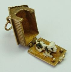 A 1960s English 9ct gold charm of a kennel that opens to reveal an enamel painted black & white spotty dog inside, hallmarked for 1964 by GJLd.